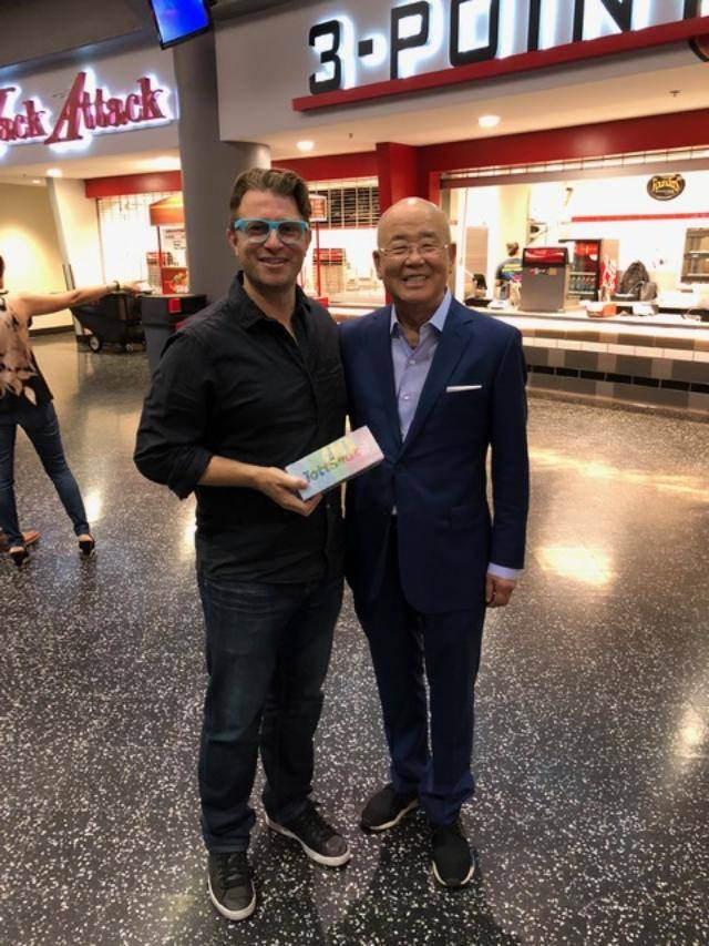 Dorian Levy stands with Hae Un Lee, owner of Lee's Discount Liquor, at the Thomas and Mack Arena. (courtesy)