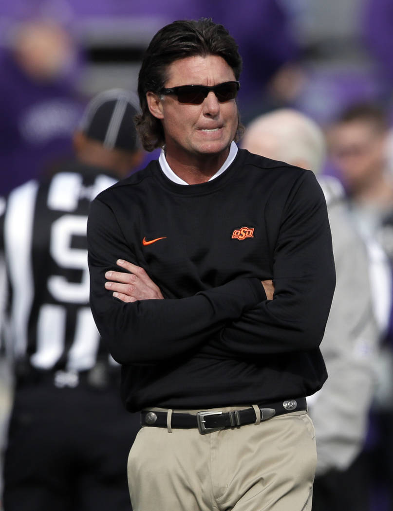 Oklahoma State head coach Mike Gundy watches his team warm up before an NCAA college football game against Kansas State in Manhattan, Kan., Saturday, Oct. 13, 2018. (AP Photo/Orlin Wagner)