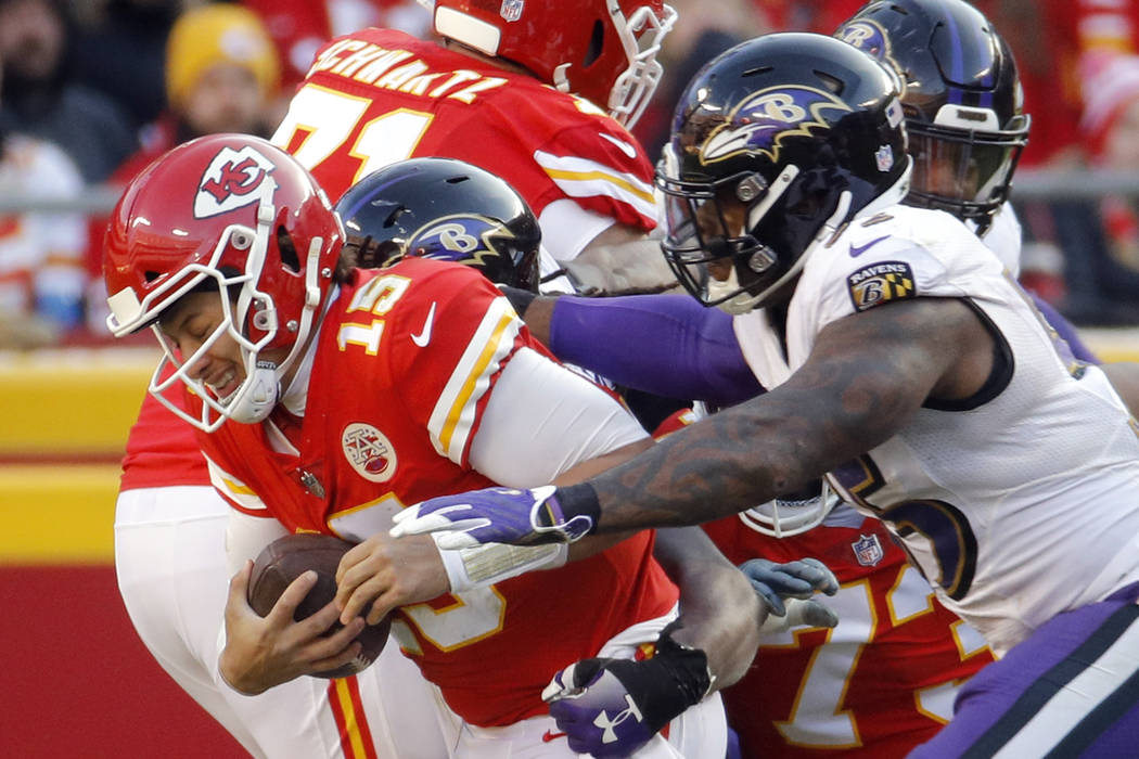 Kansas City Chiefs quarterback Patrick Mahomes (15) is sacked by Baltimore Ravens linebacker Za'Darius Smith, rear, and linebacker Terrell Suggs, right, during the second half of an NFL football g ...