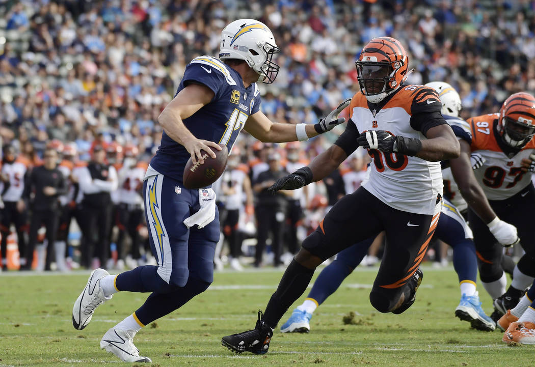 Los Angeles Chargers quarterback Philip Rivers, left, is chased by Cincinnati Bengals defensive end Carlos Dunlap during the first half of an NFL football game Sunday, Dec. 9, 2018, in Carson, Cal ...