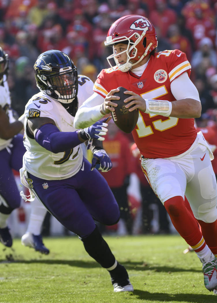 Kansas City Chiefs quarterback Patrick Mahomes (15) is pursued by Baltimore Ravens outside linebacker Terrell Suggs (55) during an NFL football game in Kansas City, Mo., Sunday, Dec. 9, 2018. (AP ...