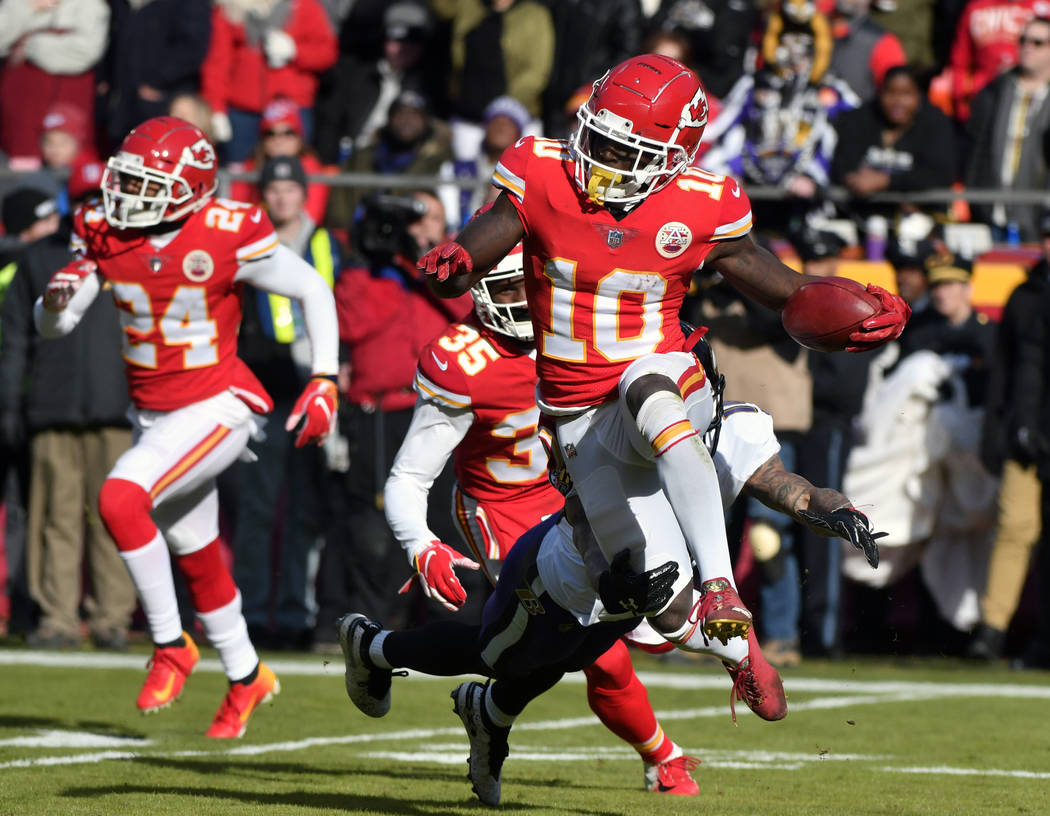 FILE - In this Dec. 9, 2018, file photo, Kansas City Chiefs wide receiver Tyreek Hill (10) runs past a tackle attempt by Baltimore Ravens' Chris Moore, rear, during the first half of an NFL footba ...