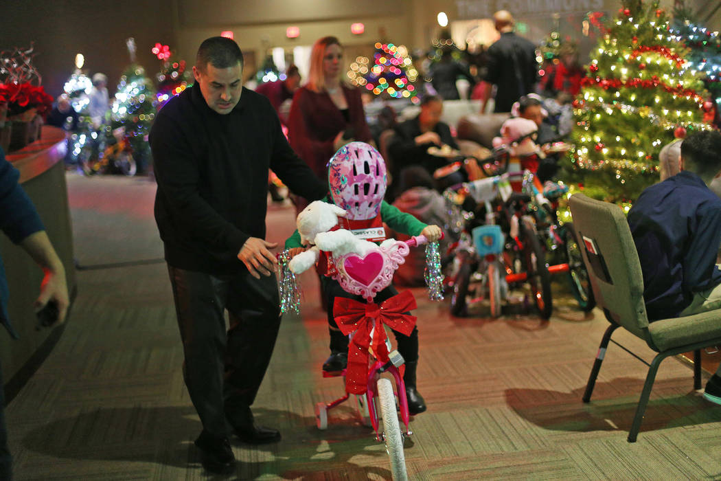 "Johnny Carranza helps his daughter Angelina Carranza, 5, ride her new bike at an event hosted by HOPE for Prisoners and the Nevada Department of Corrections that set up 50 ""living rooms"" ..."