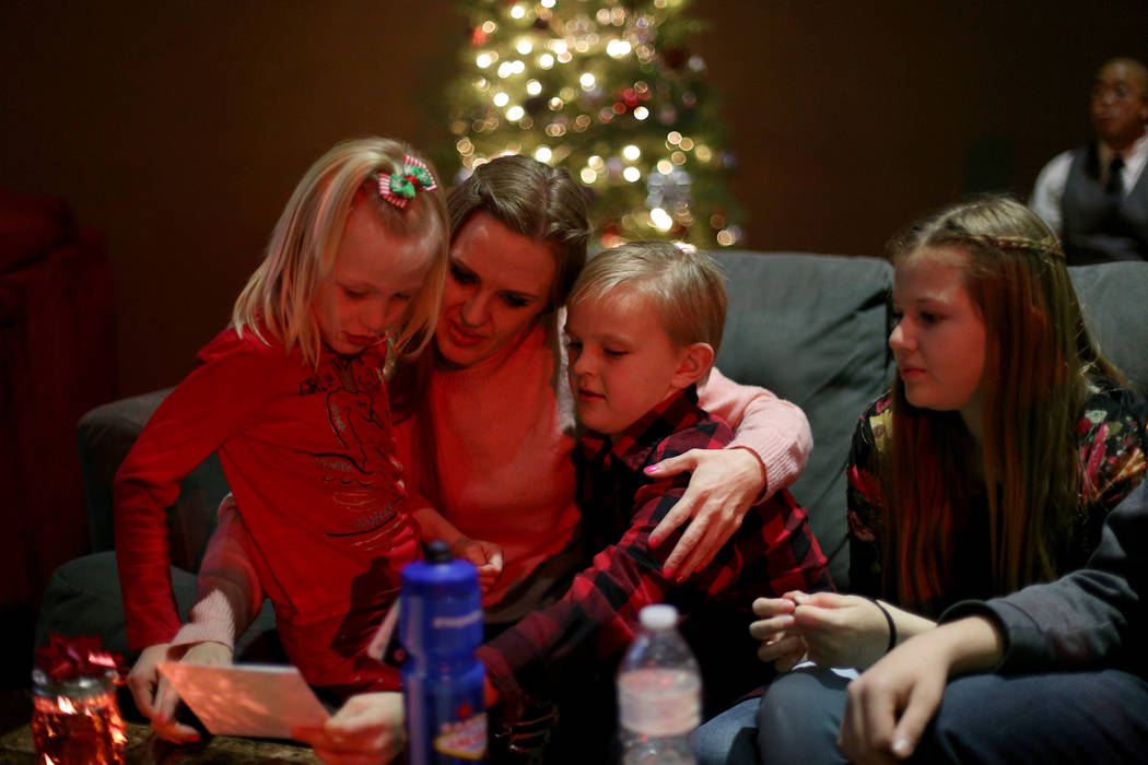 Tangila Scott, center, holds her children Ariana Hawkins, 6, left, and Landon Scott, 9, right, next to Jennessa Scott, 12, at an event hosted by HOPE for Prisoners and the Nevada Department of Co ...