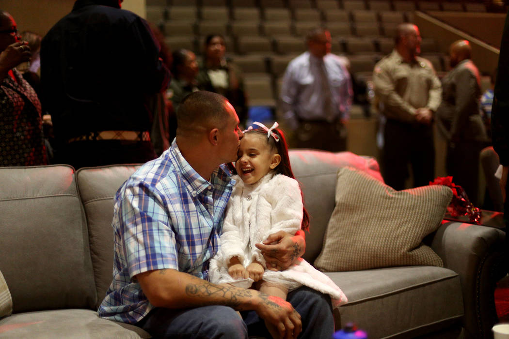 "Leonard Simons kisses his daughter Taylor Simons, 4, at an event hosted by HOPE for Prisoners and the Nevada Department of Corrections that set up 50 ""living rooms"" for Christmas at The ..."