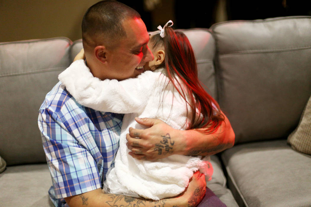 "Leonard Simons holds his daughter Taylor Simons, 4, at an event hosted by HOPE for Prisoners and the Nevada Department of Corrections that set up 50 ""living rooms"" for Christmas at The C ..."