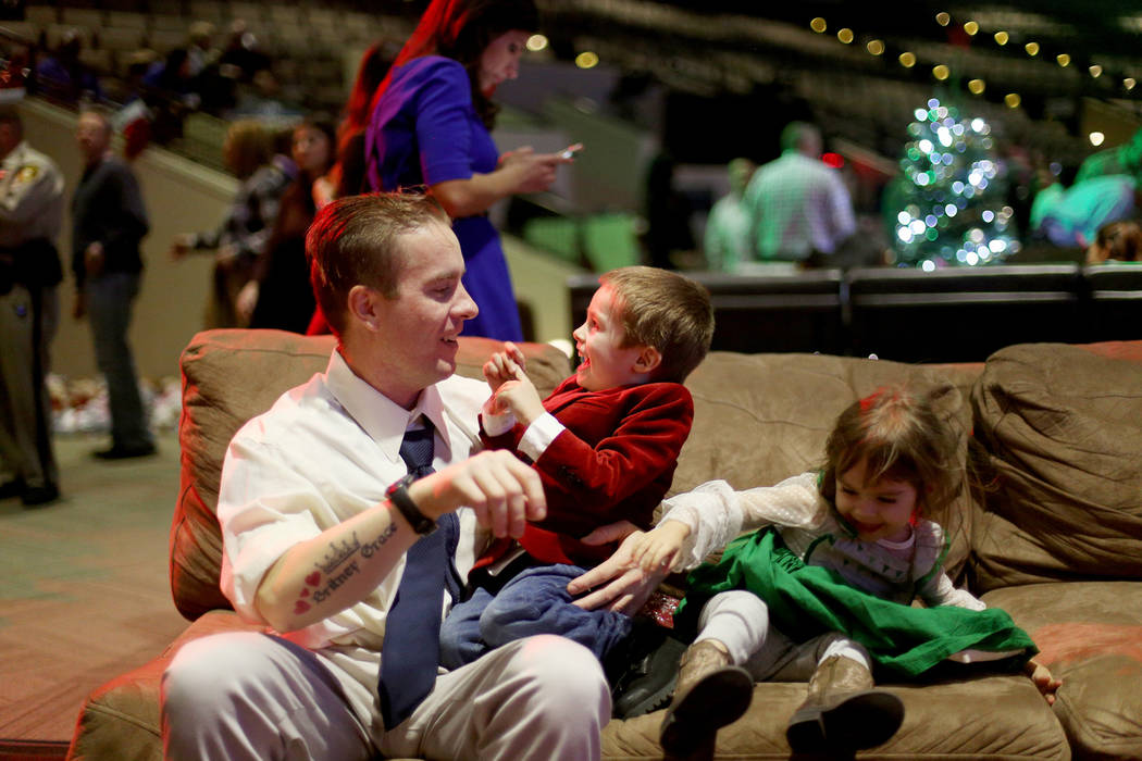 "Andrew Morris plays with his children Benjamin Morris, 3, and Britney Grace, 2, at an event hosted by HOPE for Prisoners and the Nevada Department of Corrections that set up 50 ""living rooms& ..."