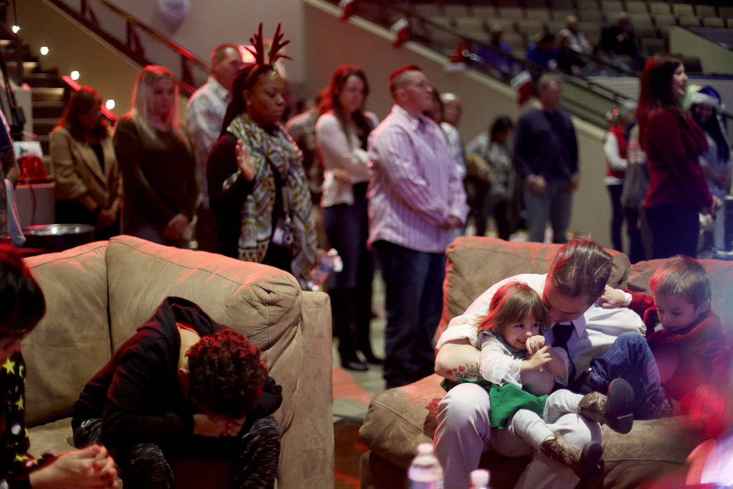 "Andrew Morris holds his children Britney Grace, 2, and Benjamin Morris, 3, as people pray at an event hosted by HOPE for Prisoners and the Nevada Department of Corrections that set up 50 ""liv ..."