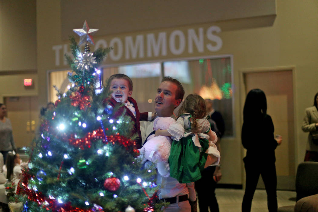 Andrew Morris holds his children Benjamin Morris, 3, and Britney Grace, 2, up to a Christmas tree at an event hosted by HOPE for Prisoners and the Nevada Department of Corrections that set up 50 & ...
