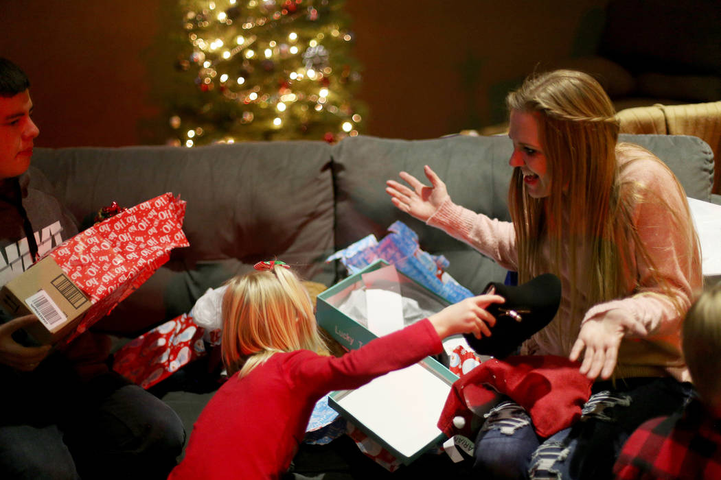 Tangila Scott opens gifts with her daughter Ariana Hawkins, 6, and her son Jacob Hawkins, 15, at an event hosted by HOPE for Prisoners and the Nevada Department of Corrections that set up 50 &quot ...