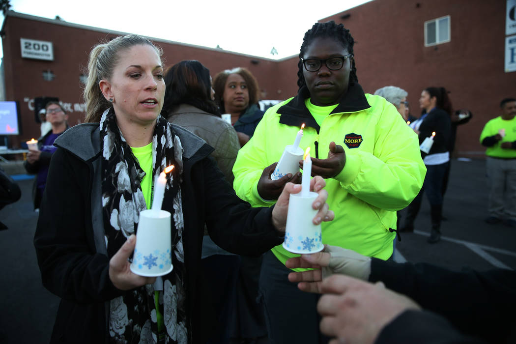 Melissa Marvelle, left, and Sunnie Ennis, with Help of Southern Nevada, light up their candles during the 23rd Annual Homeless Candlelight Vigil at the CARE Complex in Las Vegas, Thursday, Dec. 13 ...