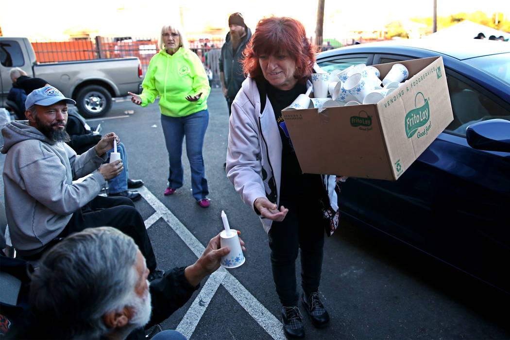 Mary Spriggs, volunteer with Straight From the Streets, hands out candles during the 23rd Annual Homeless Candlelight Vigil at the CARE Complex in Las Vegas, Thursday, Dec. 13, 2018. Erik Verduzco ...