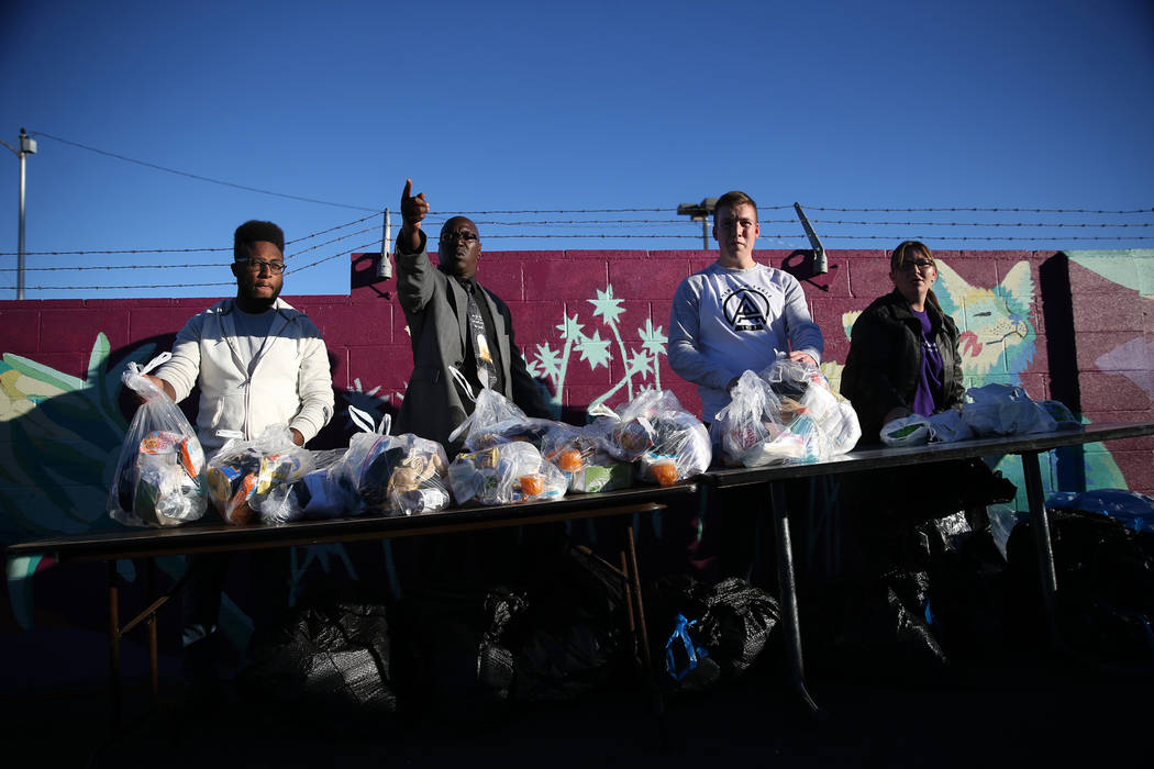 Volunteers from left, Jeremiah Randle-El, DeMarko Pace, Derek Anderson, and Jennifer Martinez, get ready to hand out care packages for people at the CARE Complex in Las Vegas during the 23rd Annua ...