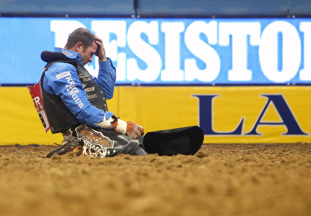 "Steven Dent of Mullen, Neb. (18) sits on the ground after falling off ""Lil' Red Hawk"" while competing in Bareback Riding during the sixth go-round of the National Finals Rodeo at the Tho ..."