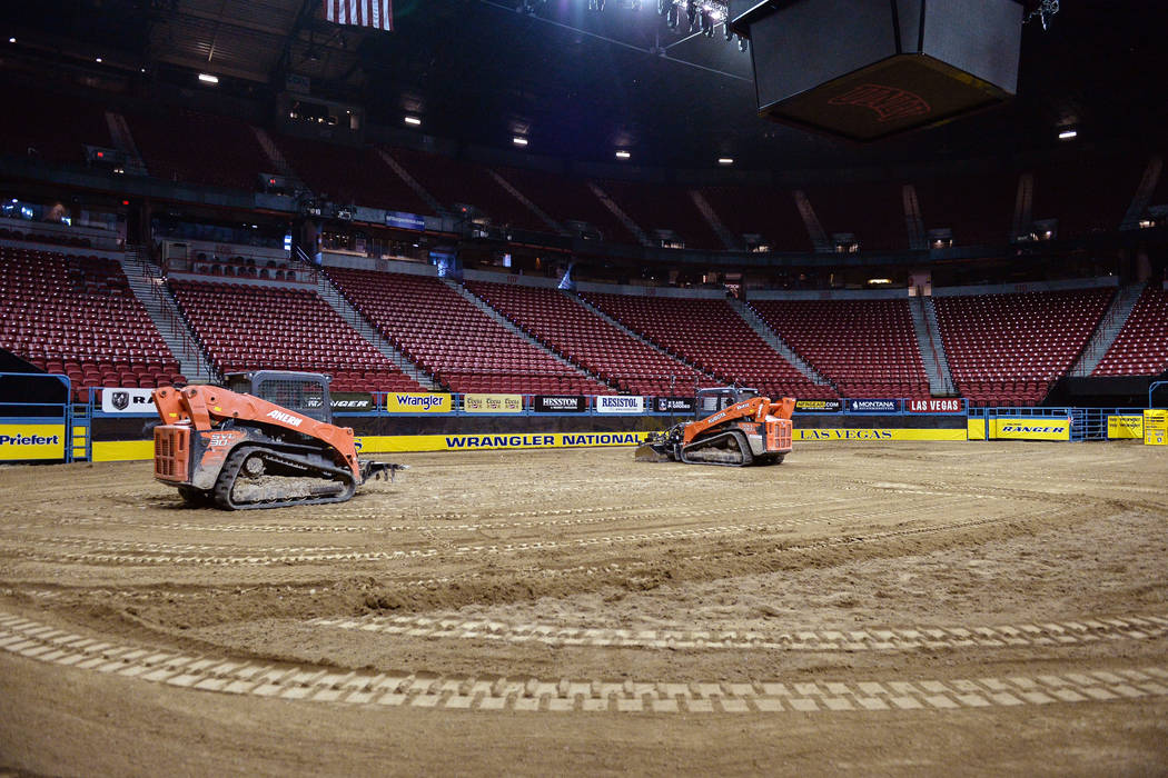Maintenance workers level out the dirt in the arena in preparation for the sixth go-round of the National Finals Rodeo at Thomas & Mack Center in Las Vegas, Tuesday, Dec. 11, 2018. Caroli ...