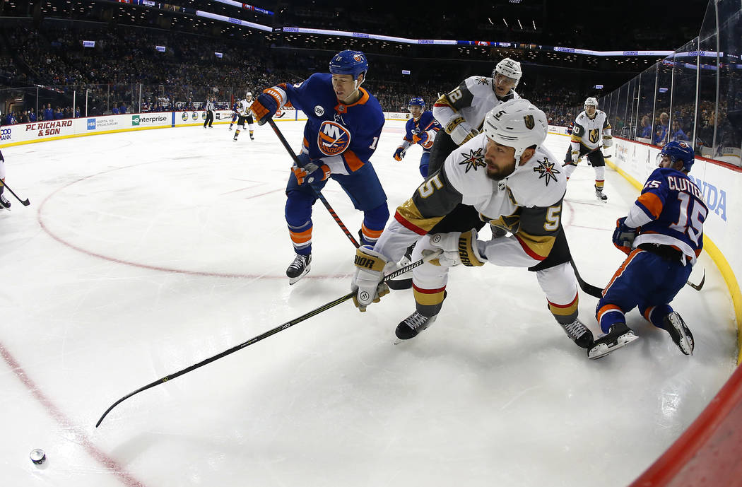 Vegas Golden Knights defenseman Deryk Engelland (5) plays the puck against New York Islanders left wing Matt Martin (17) and right wing Cal Clutterbuck (15) during the second period of an NHL hock ...