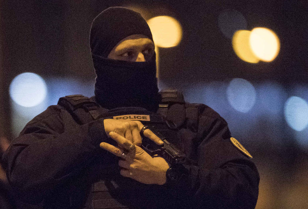 A hooded police officer holds his gun in Strasbourg, eastern France, Thursday Dec. 13, 2018. A top French official says a man has been killed in a shootout with police in Strasbourg, but he has no ...