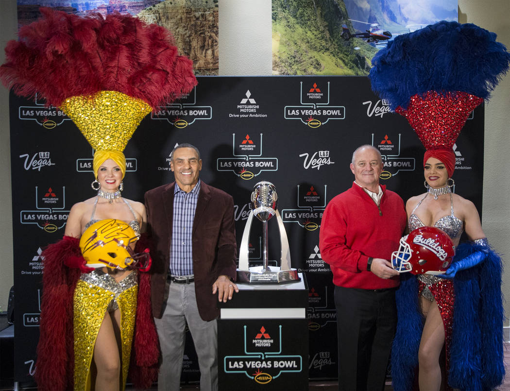Arizona State head coach Herm Edwards, second from left, and Fresno State head coach Jeff Tedford take photos on Monday, Dec. 11, 2018, at Maverick Helicopters, in Las Vegas. Benjamin Hager Las V ...