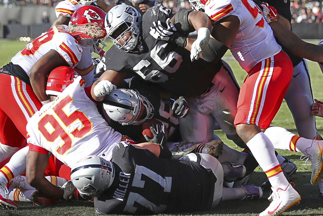Oakland Raiders running back Doug Martin, center, scores a touchdown behind guard Gabe Jackson (66) during the first half of an NFL football game against the Kansas City Chiefs in Oakland, Calif., ...