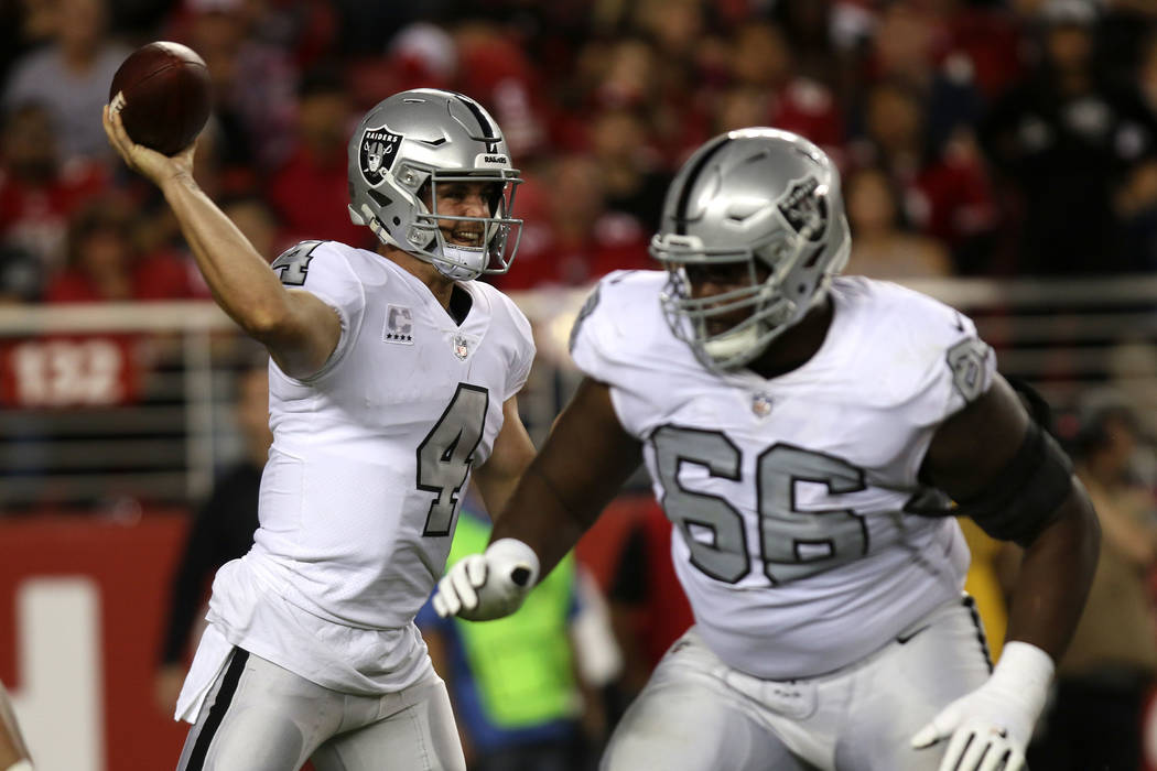 Oakland Raiders quarterback Derek Carr (4) throws the football as offensive guard Gabe Jackson (66) blocks for him during the first half of their NFL game in Santa Clara, Calif., Thursday, Nov. 1, ...