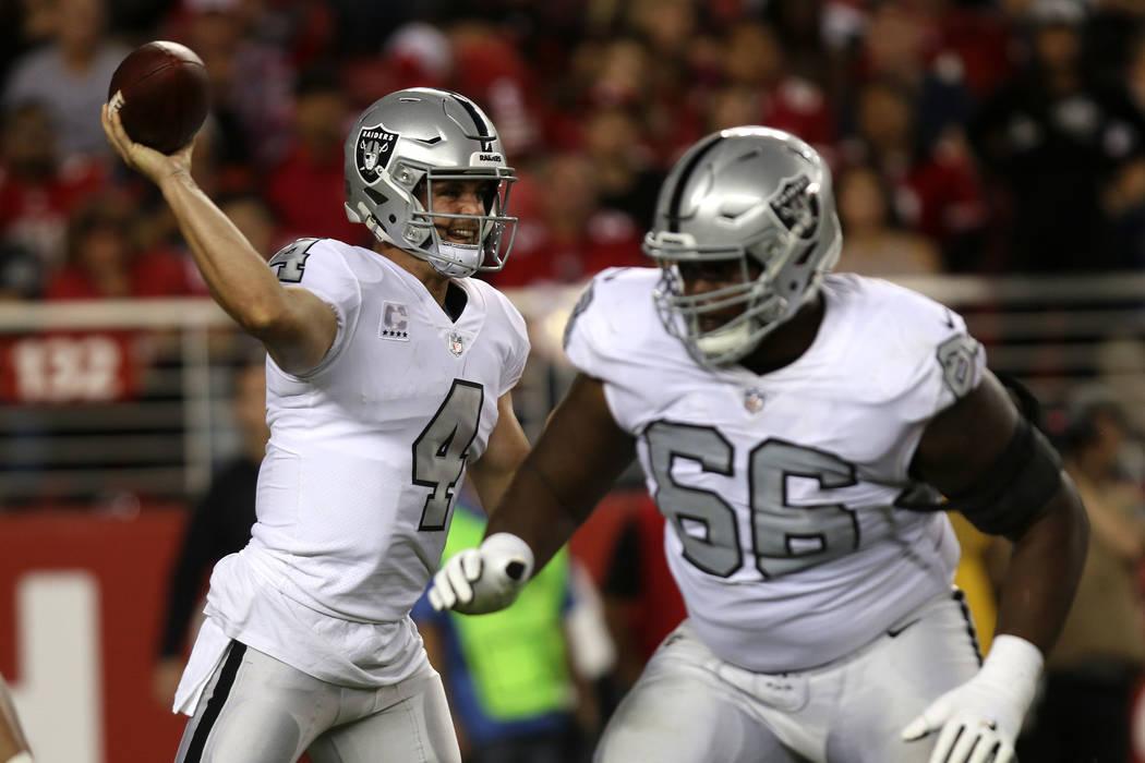 Oakland Raiders quarterback Derek Carr (4) throws the football as offensive guard Gabe Jackson (66) blocks for him during the first half of their NFL game in Santa Clara, Calif., Thursday, Nov. 1, ...
