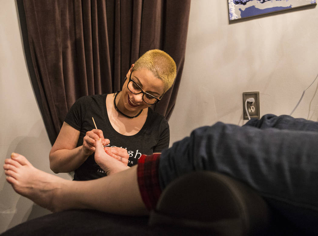 Andrea Lipomi, owner of Feetish Spa Parlor, works on client Ginger Bruner during a pedicure session in the Emergency Arts building in downtown Las Vegas on Thursday, Dec. 13, 2018. Chase Stevens L ...