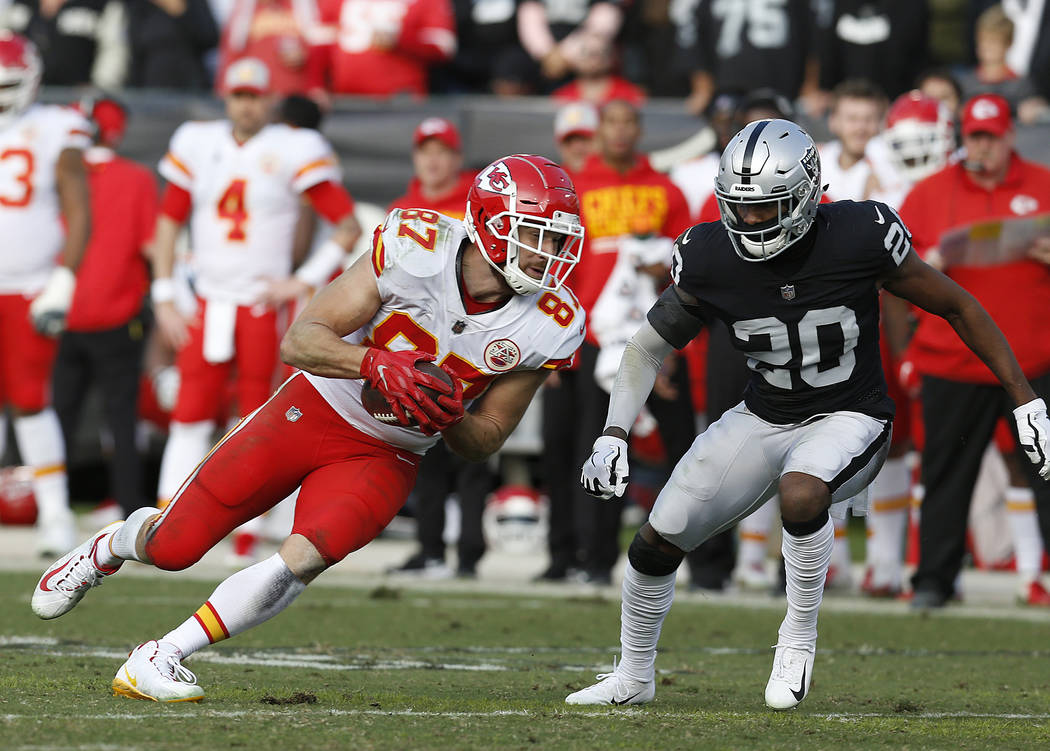 Kansas City Chiefs tight end Travis Kelce (87) runs in front of Oakland Raiders cornerback Daryl Worley (20) during the second half of an NFL football game in Oakland, Calif., Sunday, Dec. 2, 2018 ...