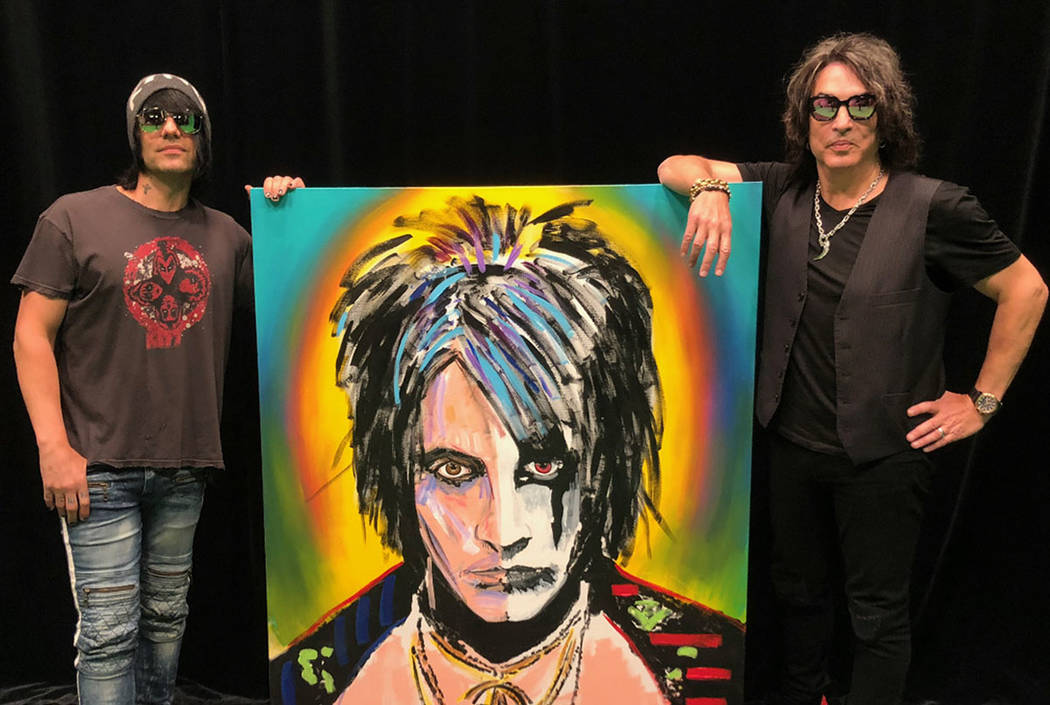 """Criss Angel and Paul Stanley are shown with the """"Split Face"""" painting Stanley has created and donated to Angel for display at his new theater at Planet Hollywood. (Criss Angel)"""