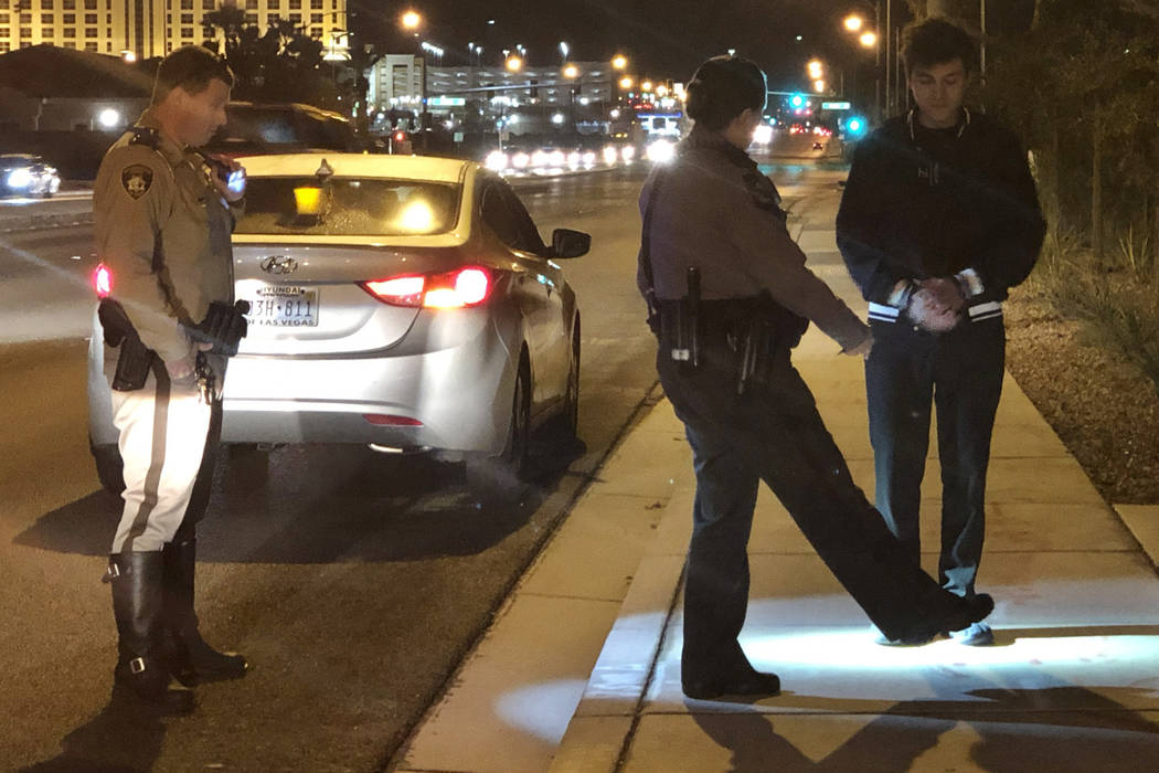 Nevada Highway Patrol Trooper Deborah Huff instructs a suspected impaired driver in field sobriety tests while Las Vegas police officer Mike Thiele looks on in the south valley on December 7, 2018 ...