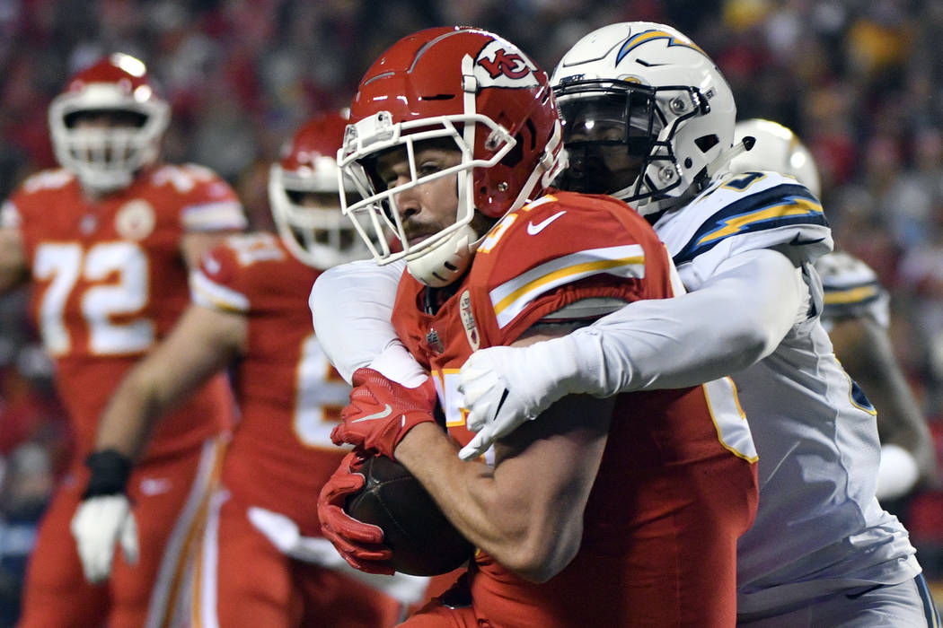 Kansas City Chiefs tight end Travis Kelce (87) is tackled by Los Angeles Chargers linebacker Jatavis Brown (57) during the first half of an NFL football game in Kansas City, Mo., Thursday, Dec. 13 ...