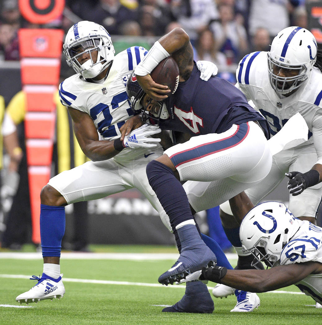 Houston Texans quarterback Deshaun Watson (4) is tackled by Indianapolis Colts' Kenny Moore II (23), Kemoko Turay (57) and Denico Autry during the first half of an NFL football game Sunday, Dec. 9 ...
