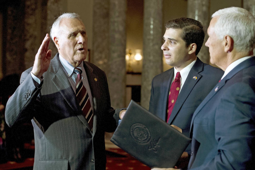 Vice President Mike Pence, right, administers the oath of office to Sen. Jon Kyl, R-Ariz., while his grandson Christopher Gavin holds a Bible, during a ceremonial swearing-in at the Old Senate Cha ...