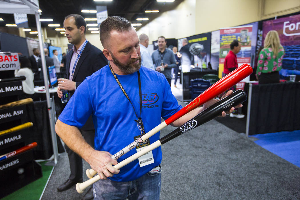 Larry Thein of the Tat2 Bat Company shows off a pair of fungo bats during the baseball trade show at Major League Baseball's winter meetings at Mandalay Bay in Las Vegas on Tuesday, Dec. 11, 2018. ...