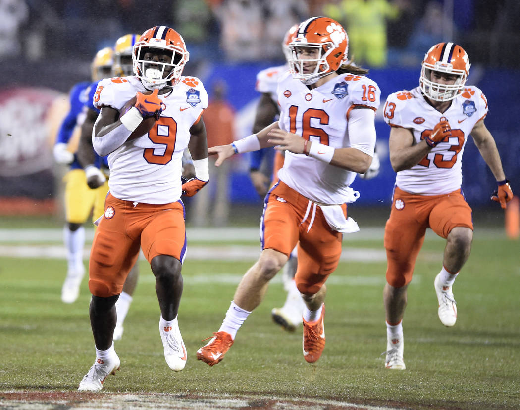 Clemson's Travis Etienne (9) runs for a touchdown against Pittsburgh as Trevor Lawrence (16) follows in the first half of the Atlantic Coast Conference championship NCAA college football game in C ...