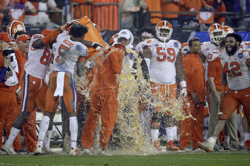 Players dunk Clemson head coach Dabo Swinney, center, in the closing moments of the second half of the Atlantic Coast Conference championship NCAA college football game against Pittsburgh in Charl ...