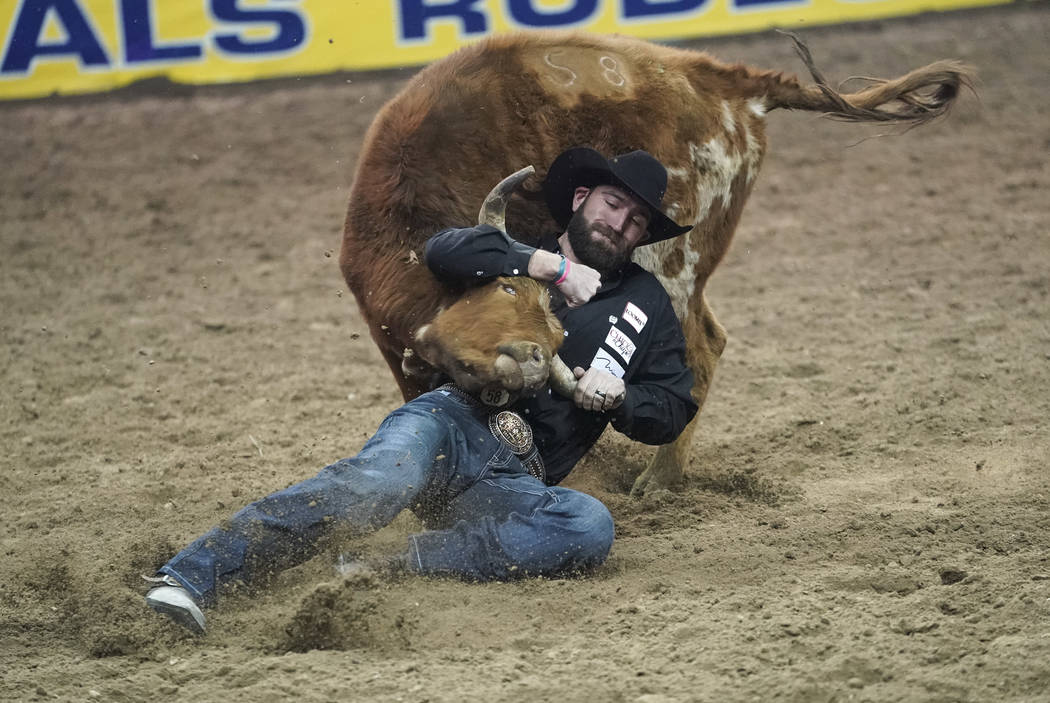 Bridger Chambers of Stevensville, Mont. (86) competes in the steer wrestling event during the eighth go-round of the National Finals Rodeo at the Thomas & Mack Center in Las Vegas on Thursday, Dec ...