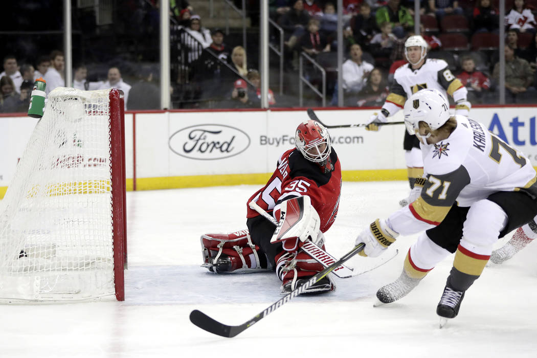 Vegas Golden Knights center William Karlsson (71), of Sweden, scores a goal against New Jersey Devils goaltender Cory Schneider (35) during the first period of an NHL hockey game, Friday, Dec. 14, ...