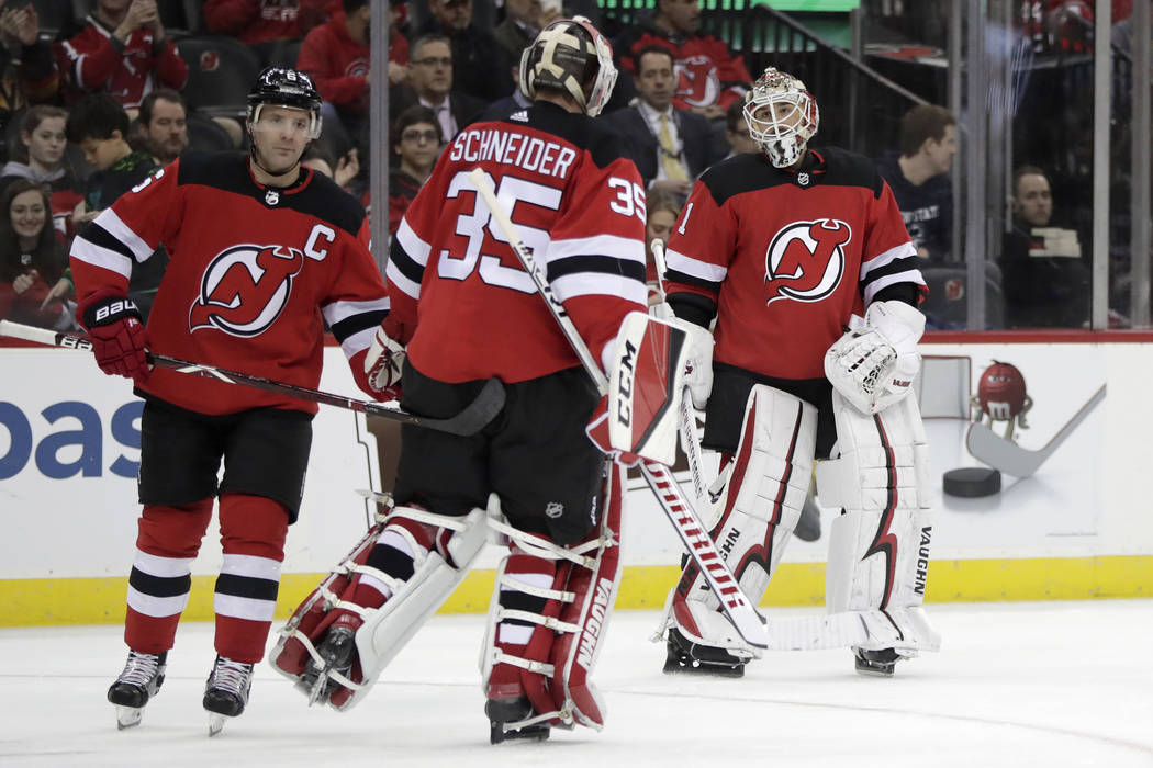 New Jersey Devils goaltender Keith Kinkaid, right, takes the ice while switching out with goaltender Cory Schneider, center, during the first period of an NHL hockey game, Friday, Dec. 14, 2018, i ...