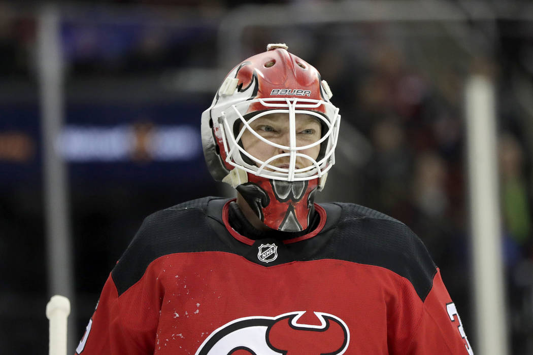 New Jersey Devils goaltender Cory Schneider reacts after giving up a goal to Vegas Golden Knights center William Karlsson, of Sweden, during the first period of an NHL hockey game, Friday, Dec. 14 ...