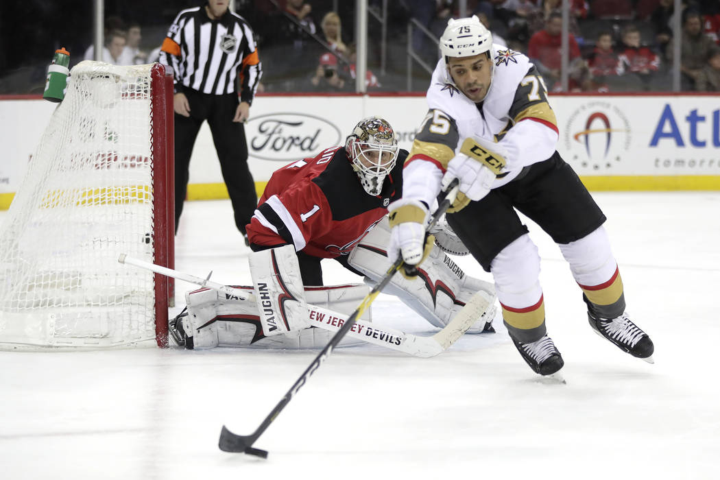 New Jersey Devils goaltender Keith Kinkaid, left, keeps watch as Vegas Golden Knights right wing Ryan Reaves (75) controls the puck during the first period of an NHL hockey game, Friday, Dec. 14, ...