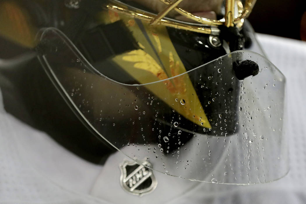 Water beads on the neck shield of Vegas Golden Knights goaltender Marc-Andre Fleury's mask during the second period of an NHL hockey game against the New Jersey Devils, Friday, Dec. 14, 2018, in N ...