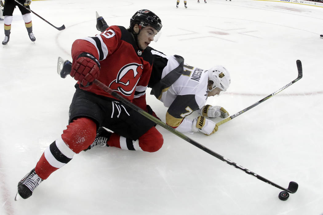 New Jersey Devils center Nico Hischier (13), of Switzerland, and Vegas Golden Knights center William Karlsson (71), of Sweden, fall to the ice while competing for the puck during the second period ...