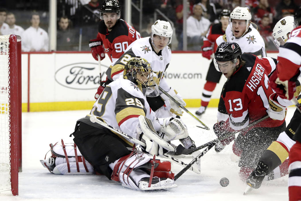 New Jersey Devils center Nico Hischier (13), of Switzerland, attacks as Vegas Golden Knights goaltender Marc-Andre Fleury (29) defends his net during the second period of an NHL hockey game, Frida ...