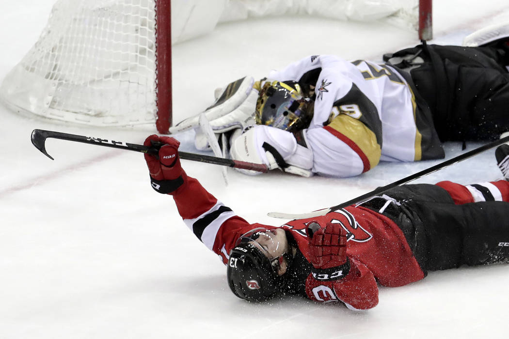 New Jersey Devils center Nico Hischier, bottom, of Switzerland, celebrates after scoring the winning goal against Vegas Golden Knights goaltender Marc-Andre Fleury, top, during overtime of an NHL ...