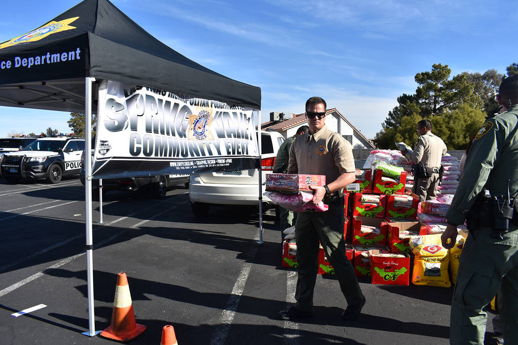 Brad Strobehn, an officer with the Metropolitan Police Department's Spring Valley Command, hauls supplies during the rice drive Dec. 13 at Korea Town Plaza. (Rachel Spacek/Las Vegas Review-Journal ...