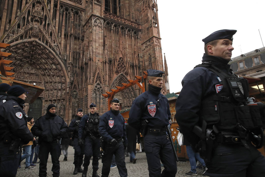French riot police officers patrol outside the cathedral as the Christmas market reopens in Strasbourg, eastern France, Friday, Dec.14, 2018. The man authorities believe killed three people during ...