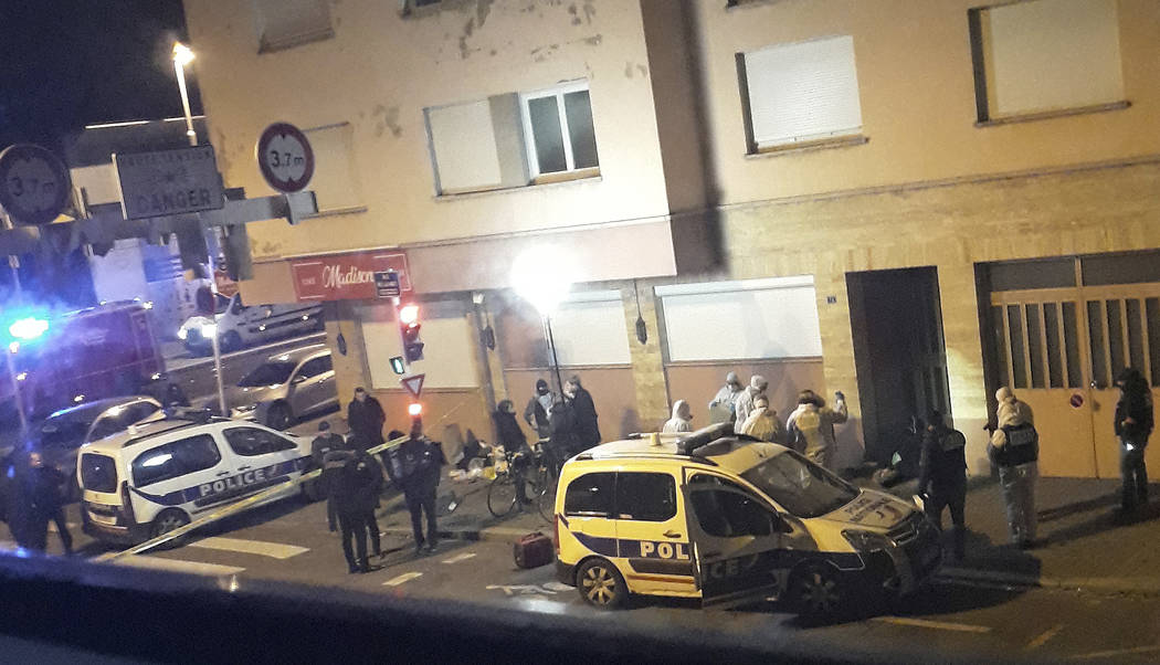 French police officers gather near the dead body of a man lying in the doorway of a building after a shootout with police in Strasbourg, eastern France, Thursday, Dec. 13, 2018. The dead man was s ...