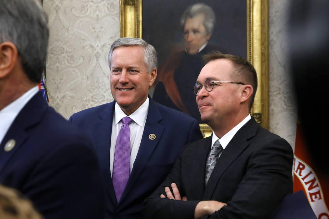 Mick Mulvaney, right, director of the Office of Management and Budget and Rep. Mark Meadows, R-N.C., attend a bill signing by President Donald Trump in the Oval Office, Tuesday, Dec. 11, 2018, in ...
