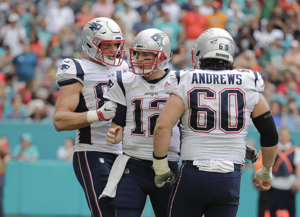 New England Patriots quarterback Tom Brady (12) is congratulated tight end Rob Gronkowski (87) an center David Andrews (60), after throwing a touchdown, during the first half of an NFL football ga ...