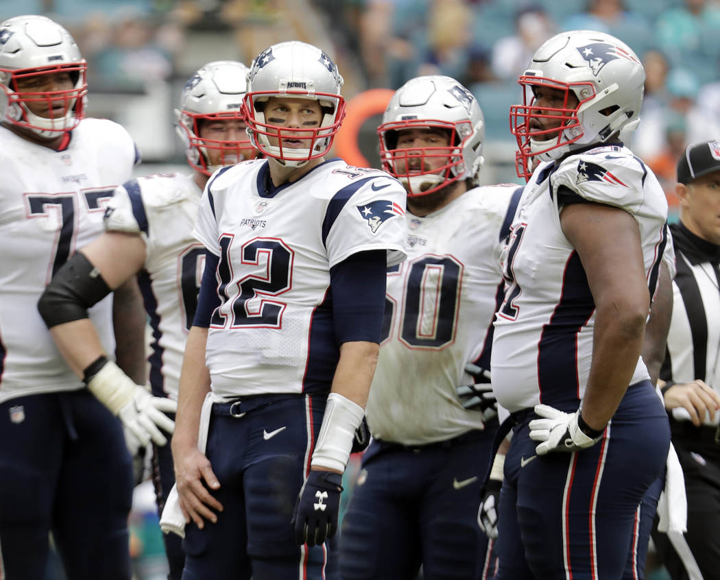 New England Patriots quarterback Tom Brady (12) and the offensive line, wait for play to resume, during the second half of an NFL football game against the Miami Dolphins, Sunday, Dec. 9, 2018, in ...